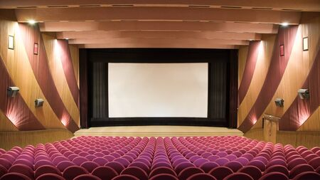 PR (property release) available. Empty cinema auditorium with line of chairs and projection screen. Ready for adding your own picture. Front view.