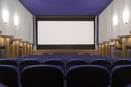 projection screen: Empty cinema auditorium with line of chairs and projection screen. Ready for adding your own picture. Front view. Stock Photo