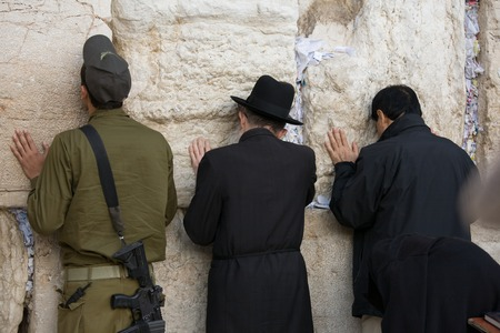 hebrew script: Praying man in Jerusalem Western Wall
