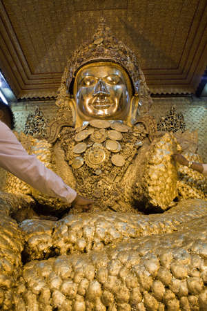 man made structure: Gold Buddha statue thick covered by gold leafs from prayers donations. Maha Mayat Muni temple, Mandalay, Burma.