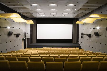 PR (property release) available. Empty cinema auditorium with line of yellow chairs, stage and projection screen. Ready for adding your own picture.