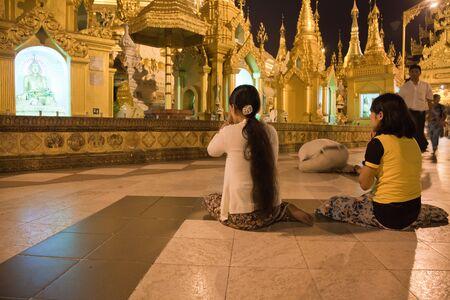 buddhist structures: RANGOON, BURMA - MARCH 2, 2011: The biggest Buddhist temple Shwedagon pagoda at night lighting with praying Buddhist people, Rangoon, Burma.