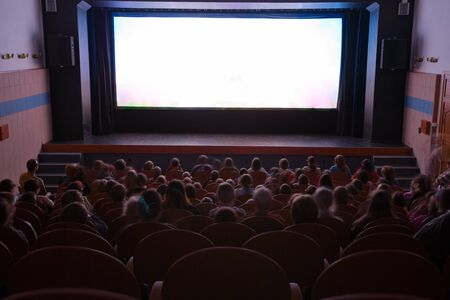 watching movie: Cinema auditorium with people in chairs watching movie performance. Ready for adding your own picture. Stock Photo