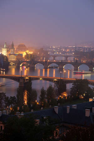 vltava: Twilight on Vltava river in Prague with bridges and boats. Stock Photo