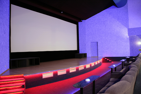 Empty blue cinema auditorium with red stage and projection screen. Ready for adding your own picture.