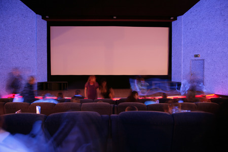 Blue cinema auditorium with red stage and projection screen. With crowding people. Ready for adding your own picture. photo