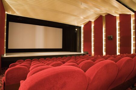 Empty cinema auditorium with line of chairs and projection screen. Ready for adding your own picture. Front view. Standard-Bild