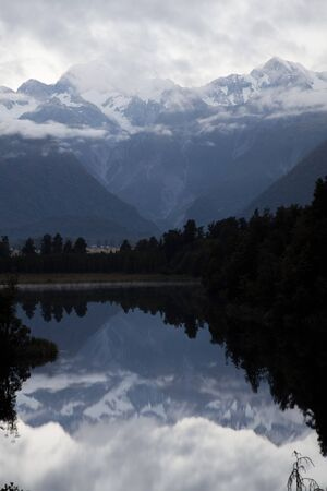 fox glacier: Sunrise with flowing clouds and glacier reflection in Fox Glacier, New Zealand, Southern Island.