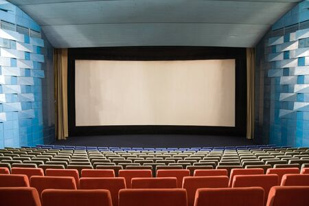 projection screen: PR (property release) available. Empty cinema auditorium with line of red chairs, stage and projection screen. Ready for adding your own picture.