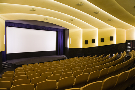 projection screen: Empty cinema auditorium with line of chairs and projection screen. Ready for adding your own picture. Side view. Stock Photo