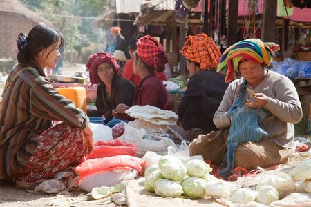 food state: BURMA, SHAN STATE, SAMKAR -  FEBRUARY 25, 2011: Pa-O tribal woman in native costume are sitting on the market are selling home-made food.
