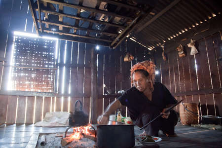 shanty: BURMA, SHAN STATE, SAMKAR -  FEBRUARY 25, 2011: Pa-O tribal woman in native costume is cooking on open fire place in her shanty kitchen. Editorial