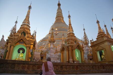 man made structure: BURMA, RANGOON, SHWEDAGON PAGODA - FEBRUARY 11, 2011: Monk woman in the biggest Buddhist temple Shwedagon pagoda. Editorial