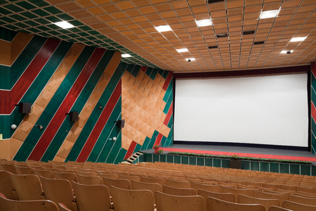 PR (property release) available. Empty cinema auditorium with line of chairs and projection screen. Ready for adding your own picture. Side view.