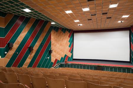 PR (Property Release) zur Verfügung. Leere Kinosaal mit der Linie der Stühle und Projektionsfläche. Bereit für Sie Ihre eigenen Bild. Seitenansicht. Standard-Bild - 39109715