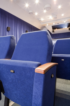PR (property release) available. Empty cinema auditorium with line of chairs. Front view.