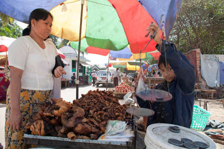 BURMA, RANGOON - FEBRUARY 13, 2011: Young boy is selling on street local market fried pork offals.