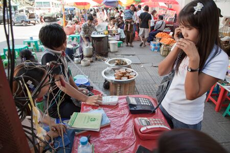 BURMA, RANGOON - FEBRUARY 13, 2011: People are making calls in local phone booth on street market.