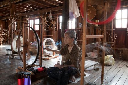 BURMA, Inle-See - 24. Februar 2011: Frau spinnt Garn in alten Weberei in Burma. Standard-Bild - 39606494