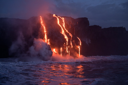 Hot lava stream is flowing into the ocean. Hawaii, Big Island. 免版税图像