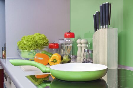 Green frying pan on modern black induction stove, cooker, hob or on cooktop in green kitchen interior. Fresh vegetables lie in the background on a gray table
