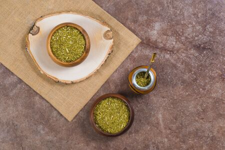 Yerba mate with bombilla in calabash and in two wooden bowls on stone background