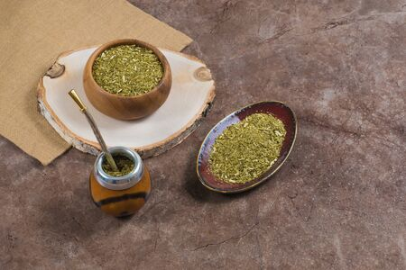 Yerba mate with bombilla in calabash and in wooden bowl and on ceramic stand on stone bakground 写真素材