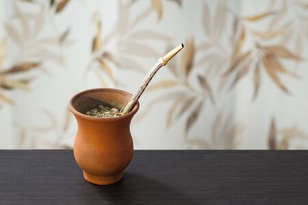 Traditional South American yerba mate in calabash with bombilla stand on wooden table.