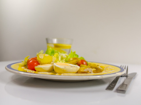 side view of a salad with potatoes, cherry tomatoes and eggs, chipped on a yellow plate, drink water with lemon, vegetarian dish