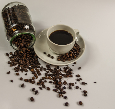 upturned: black coffee in a white cup on a saucer with an upturned jar on the coffee beans and spilled coffee beans, artistic decoration