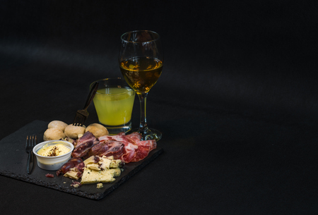 dish consisting of various kinds of meats and sausages, French cheeses, fresh crunchy bread, dip garlic, lemon juice and white wine, a great dinner