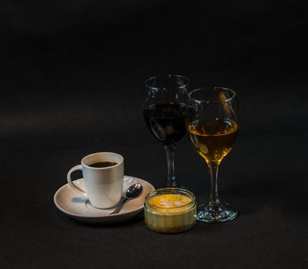 aromatische zwarte koffie in een witte kop, witte en rode wijn, zoet dessert