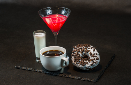 right side view on a drink cosmopolitan a glass of martini decorated with a red bow with coconut liqueur in a glass, with coffee, with two oreo doughnut on a black stone plate, party set