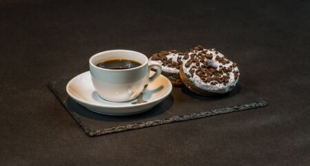left view on an aromatic black coffee in a white cup with two oreo doughnut on a black stone plate, morning set