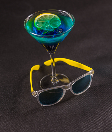 yello: colored drink, a combination of blue and green, lemon, martini glass, yellow sunglasses, party set