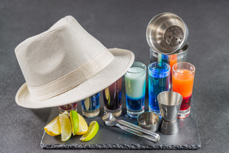 six different colored shot drinks, lined up on a black stone plate, ice cubes in shaker and ice tongs, lemon and lime, white hat, party set