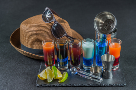 six different colored shot drinks, lined up on a black stone plate, ice cubes in shaker and ice tongs, lemon and lime, brown hat, brown sunglasses, party set