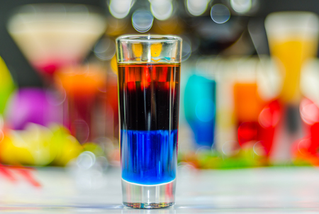 amaretto: colored drink in glass for shots, a combination of blue with red, colorful background, drink shot Stock Photo