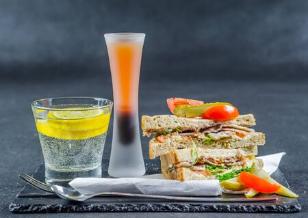 set consisting of two sandwiches malted bread with smoke flavor becon, pickles, mayonnaise, tomato, lettuce, drink with water, tasty set Stock Photo