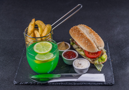 crusty white bread with sesame seeds, flavored with smoky ribsteak bbq, barbeque sauce, lettuce, tomato, three sauces, chips in a metal basket, green drink, tasty set Stock Photo