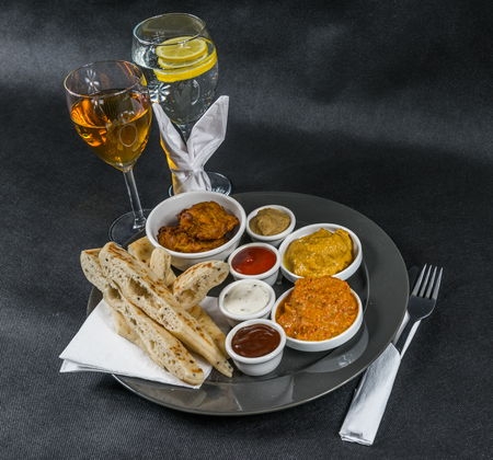 Oriental Indian set, chicken korma, chicken tikka masala, pilau rice, naan bread, four sauces, gray plate, white wine, water with lemon, sweet egg, tasty set
