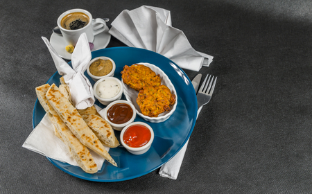 Oriental Indian set,  naan bread and onion bhaji, four sauces, blue plate, black coffee, tasty set Stock Photo
