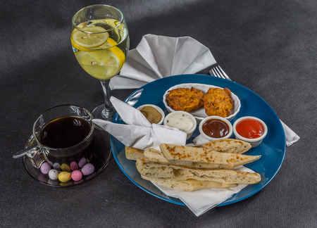 Oriental Indian set,  naan bread and onion bhaji, four sauces, blue plate, black coffee, water with lemon, tasty set Stock Photo