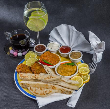 Oriental Indian set, chicken korma, chicken tikka masala, naan bread, onion bhaji, plate, coffee, water with lemon, napkin, peppers, four sauces, tasty set