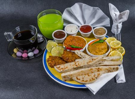 Oriental Indian set, chicken korma, chicken tikka masala, naan bread, onion bhaji, plate, coffee, green drink, napkin, peppers, four sauces, tasty set Stock Photo