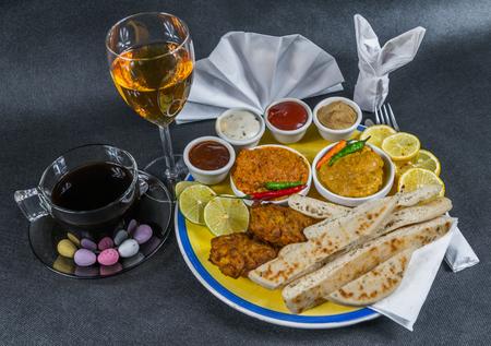 Oriental Indian set, chicken korma, chicken tikka masala, naan bread, onion bhaji, plate, coffee, white wine, napkin, peppers, four sauces, tasty set