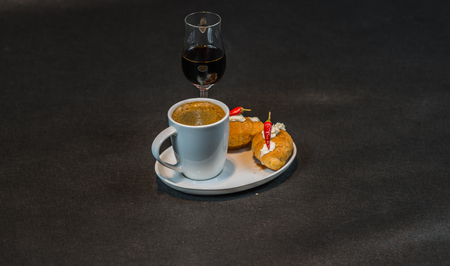 Black coffee in white cup, with croissants on saucer, liqueur, peppers, tasty set Stock Photo