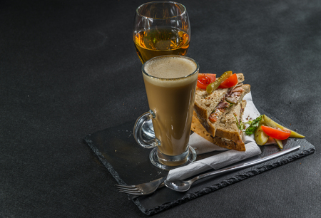 malted: set consisting of two sandwiches malted bread with smoke flavor becon, pickles, mayonnaise, tomato, lettuce, white wine with coffee latte, tasty set Stock Photo