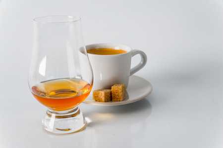 Black coffee in white cup, brown sugar cubes on saucer, whisky single malt, white background Stock Photo