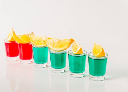 Glasses with green and red kamikaze, glamorous drinks, mixed drink poured into shot glasses, party set Stock Photo